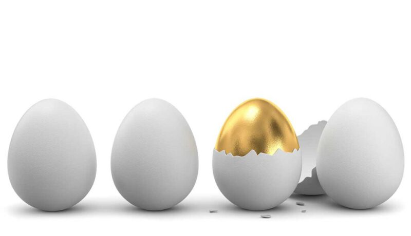 White eggs and solid gold egg with broken shell